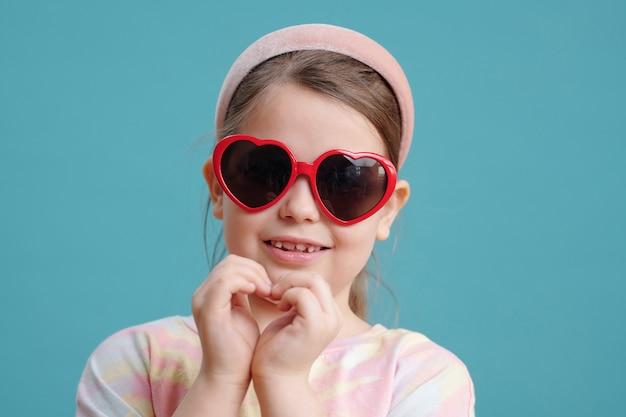 Ritratto di bambina in occhiali da sole che fa la forma del cuore dalle sue mani e sorride alla telecamera sullo sfondo blu