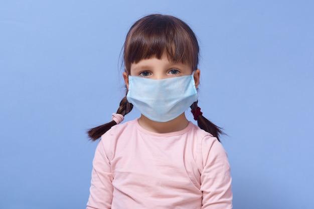 Ritratto di bambina che indossa roseshirt e maschera usa e getta sul viso, in posa