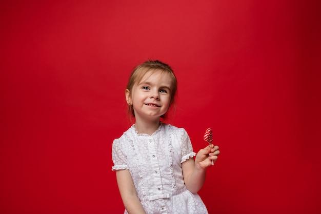 Ritratto di una bambina in un abito bianco con un lecca-lecca sul rosso