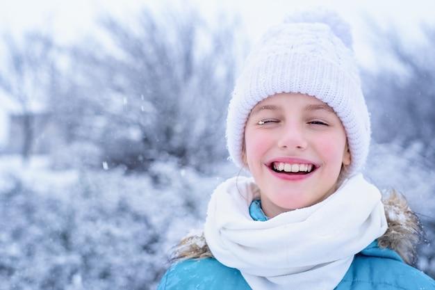 Ritratto di una bambina in abiti invernali con fiocchi di neve sulle ciglia.