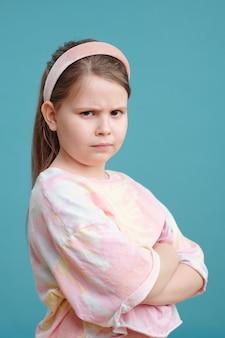 Ritratto di bambina con faccia arrabbiata in piedi con le braccia incrociate sullo sfondo blu