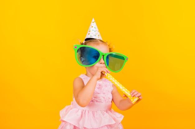Ritratto di una bambina con grandi occhiali e un cappello festivo che soffia un fischio su uno sfondo giallo con spazio per il testo