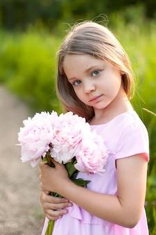 Ritratto di una bambina con un bouquet di peonie