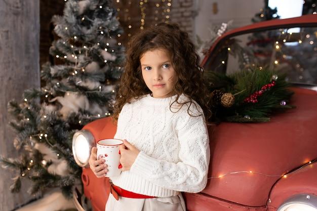 Ritratto di bambina con la tazza di natale di tee vicino all'automobile rossa e alberi di natale con luci. buon natale e buone feste