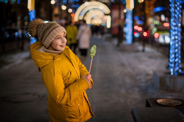 Ritratto di una bambina con il caffè in mano nel mezzo della città decorata con luci di natale