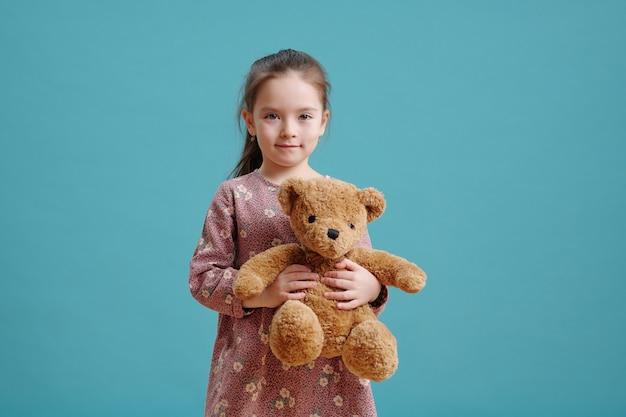 Ritratto di bambina con orsacchiotto che guarda l'obbiettivo contro lo sfondo blu