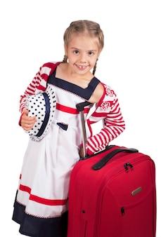 Ritratto di bambina con custodia da viaggio e cappello isolato su bianco