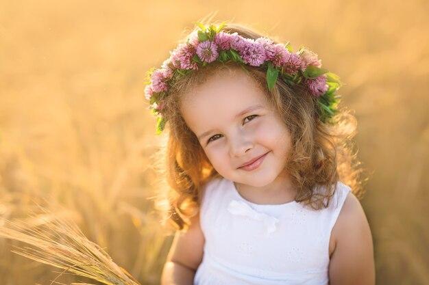 Ritratto di una bambina con una corona di trifoglio sulla testa.