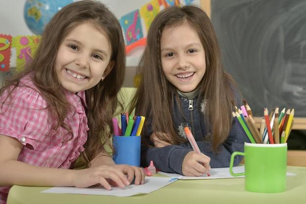 Ritratto di una bambina che disegna con matite colorate