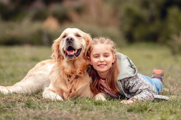 Ritratto di bambina felice sdraiata sull'erba con il cane golden retriever in primavera spring