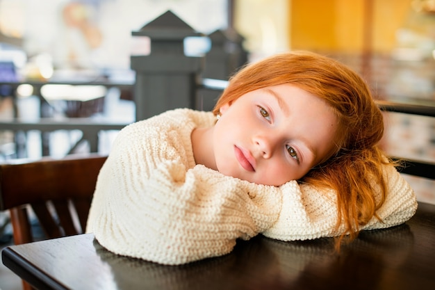 Ritratto di una piccola ragazza dai capelli rossi in attesa da sola a un tavolo in un caffè