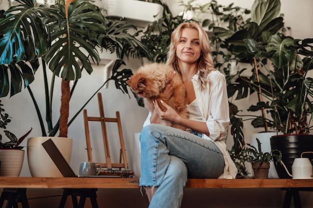 Ritratto di un gattino persiano dai capelli rossi e della sua bella proprietaria femmina. soggiorno contemporaneo e rilassante con piante d'appartamento.