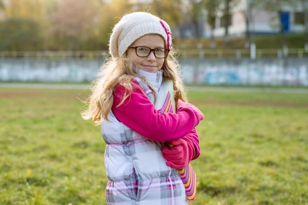 Ritratto di piccola scolara il giorno soleggiato di autunno