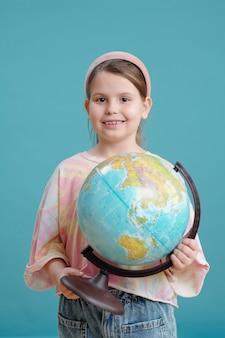 Ritratto di piccola studentessa con globo che sorride alla telecamera in piedi sullo sfondo blu