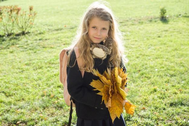 Ritratto di piccola scolara con la borsa di scuola gialla delle foglie di acero