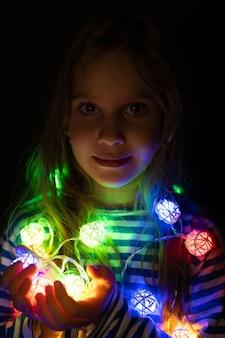 Ritratto di una bambina di sette anni che tiene una ghirlanda tra le mani vicino al viso, illuminata da luci al neon multicolori colorate di notte a casa. festa della vigilia di natale