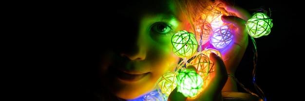 Ritratto di una bambina di sette anni che tiene una ghirlanda tra le mani vicino al viso, illuminata da luci al neon multicolori di notte a casa. celebrazione delle vacanze della vigilia di natale. striscione