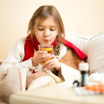 Ritratto di piccola ragazza malata sdraiata a letto e che soffia sul tè caldo