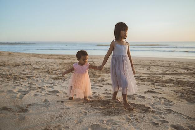 Ritratto di sorelline che godono di una vacanza sulla spiaggia