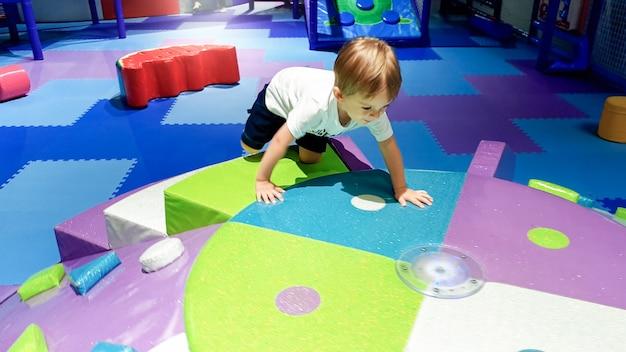 Ritratto di un bambino piccolo che striscia e gioca sul colorato parco giochi per bambini coperto di tappetini morbidi nel centro commerciale