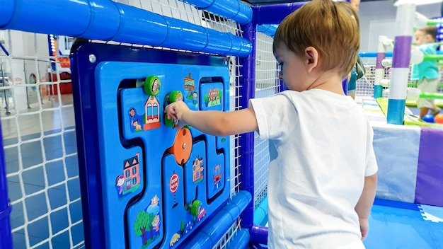 Ritratto di un bambino piccolo che gioca con un puzzle giocattolo di legno appeso al muro nel parco divertimenti del centro commerciale