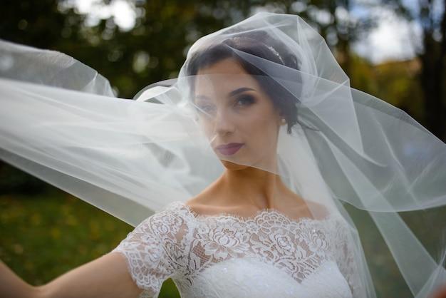 Ritratto di una sposa solitaria in un parco in autunno. la ragazza si è rifugiata sotto un velo con cui si sviluppa il vento. avvicinamento.