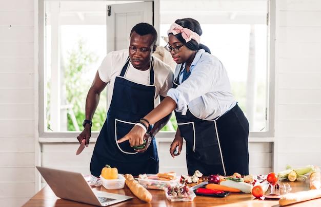 Ritratto di amore coppia afro-americana divertendosi a cucinare insieme e alla ricerca di ricetta su internet con computer portatile per preparare il gustoso mangiare in cucina a casa
