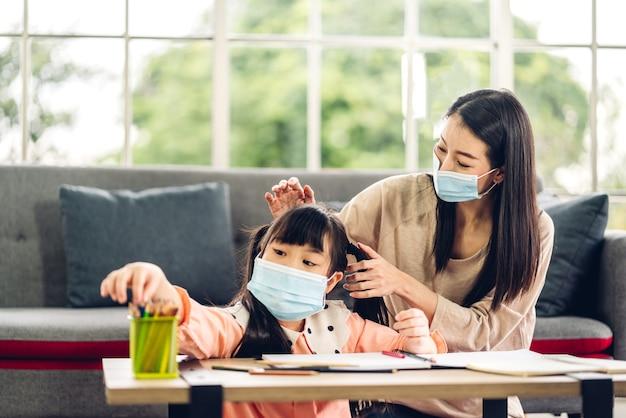 Il ritratto ama la madre di famiglia asiatica e la piccola ragazza asiatica che imparano e scrivono nel libro con la matita che fa i compiti in quarantena per il coronavirus che indossa una maschera protettiva con allontanamento sociale a casa