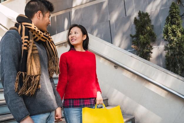 Ritratto di coppia asiatica adorabile che tiene le borse della spesa colorate e godersi lo shopping, divertirsi insieme nel centro commerciale.