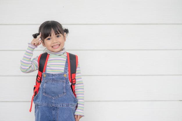 Ritratto di bella ragazza asiatica che pensa su sfondo bianco