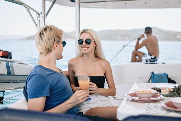 Ritratto di bella bella coppia uomo e donna, bere in un bar locale su uno yacht.