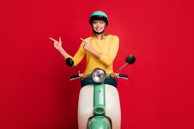Ritratto di bella ragazza allegra felice che si siede sul ciclomotore che mostra la soluzione dello spazio della copia