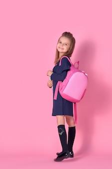 Ritratto di una bella ragazza intelligente fiduciosa con il quaderno di quaderno indossando l'uniforme scolastica