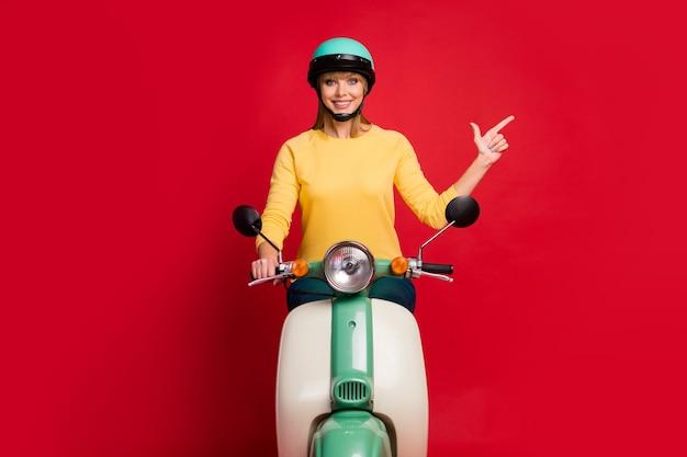 Ritratto di bella ragazza sicura di sé in sella a ciclomotore che mostra copia spazio vuoto vuoto
