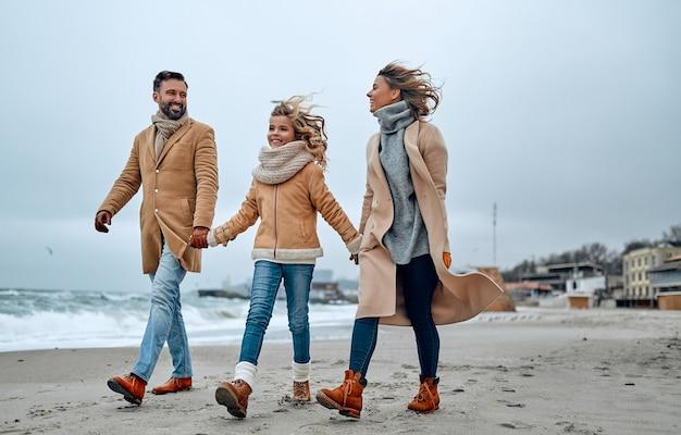 Ritratto di una bella famiglia che cammina, tenendosi per mano sulla spiaggia in inverno.