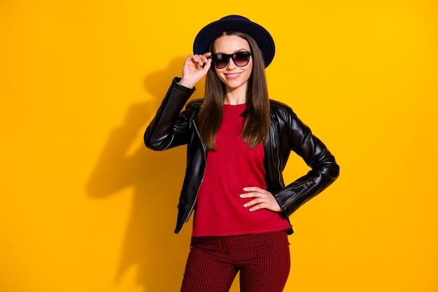 Ritratto di una bella ragazza allegra alla moda che tocca le specifiche