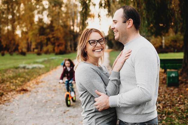 Ritratto di un adorabile padre e madre che si abbracciano e ridono mentre la loro figlia sta andando in bicicletta nel parco.