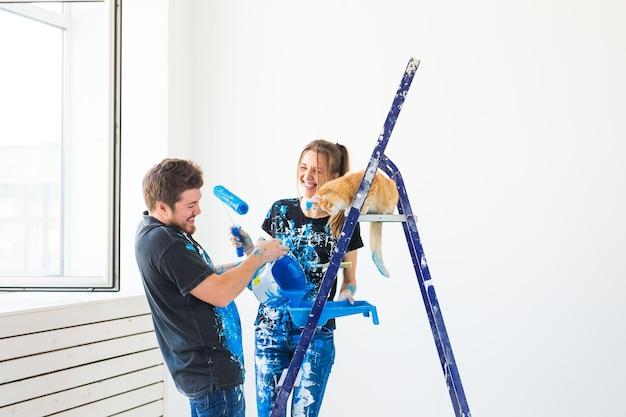 Ritratto di bella coppia divertente con il gatto che fa la ristrutturazione in appartamento.