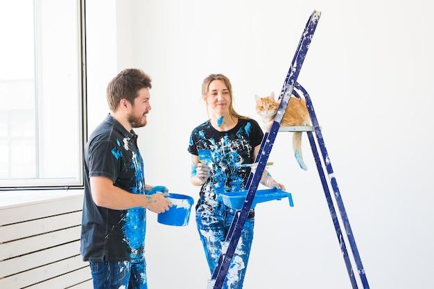 Ritratto di bella coppia divertente con il gatto che fa la ristrutturazione
