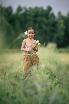 Ritratto di ragazze adorabili in abito tradizionale tailandese e mettere un fiore bianco sul suo orecchio, in piedi e tenere due loti in mano sul campo di riso, lei sorride con felicità, copia spazio