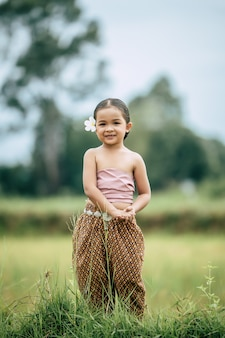 Ritratto di ragazze adorabili in abito tradizionale tailandese stand in modo educato sul campo di riso, sorride con felicità, copia spazio