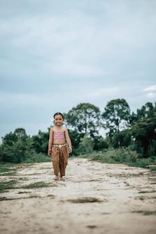 Ritratto di ragazze adorabili in abiti tradizionali tailandesi che camminano su un sentiero nella natura, sorride con felicità, copia spazio