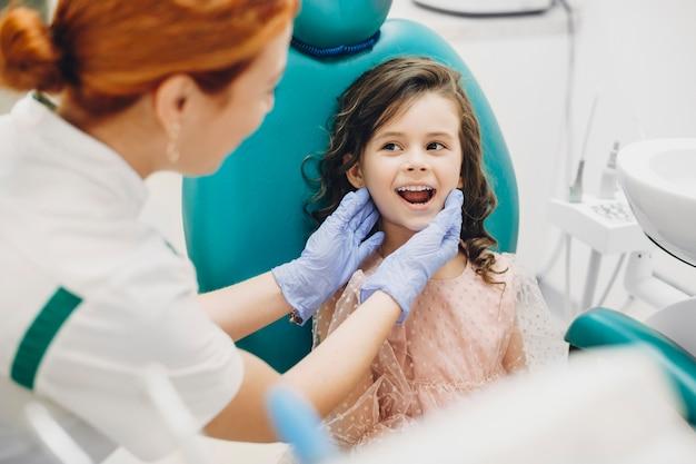 Ritratto di un adorabile ragazzino che mostra i denti al dentista pediatrico.