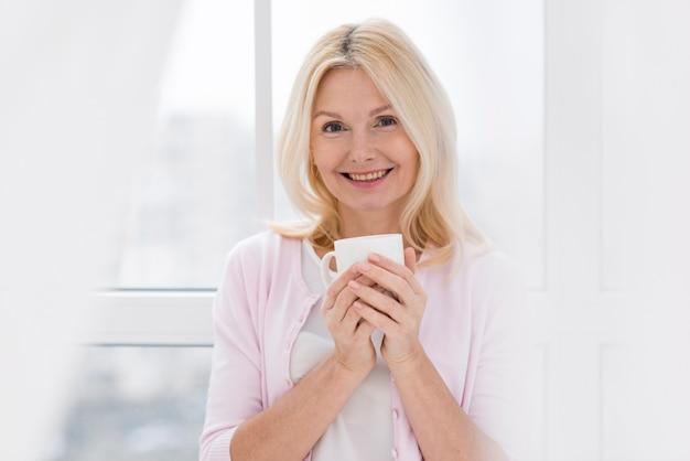 Ritratto della donna matura adorabile che tiene una tazza
