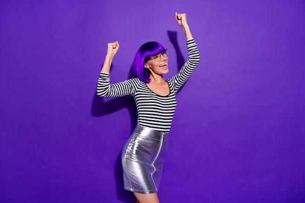 Ritratto di persona adorabile che alza i pugni urlando sì che indossa occhiali da vista isolati su sfondo viola viola