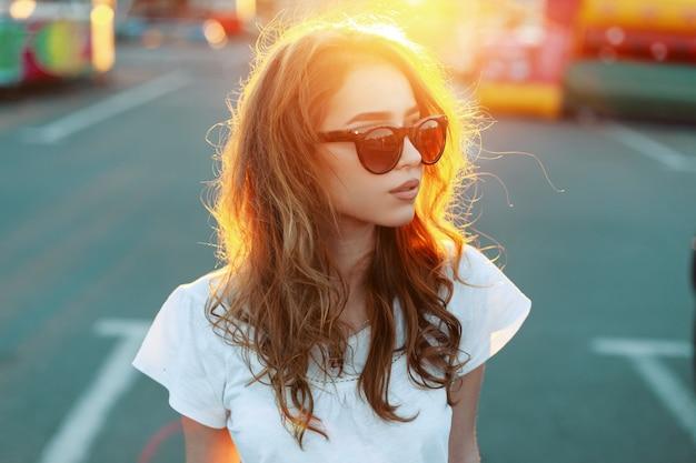 Ritratto di donna hipster bella piuttosto giovane rossa con labbra sexy in occhiali da sole alla moda in maglietta bianca