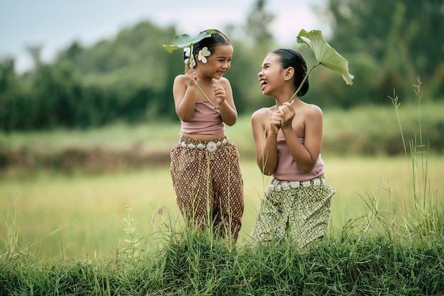 Ritratto di adorabile sorella e giovane sorella in abito tradizionale tailandese e mettere un fiore bianco sul suo orecchio, tenendo in mano una foglia di loto, ridono insieme felici sul campo di riso, copia spazio
