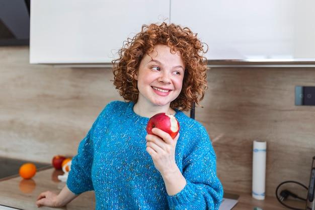 Ritratto di una bella ragazza sorridente adorabile che morde una mela nella sua cucina. giovane donna che gode della sua frutta rossa mela organica. assunzione giornaliera di vitamine con frutta, dieta e alimentazione sana