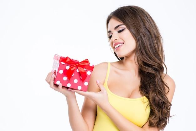 Ritratto di una donna adorabile che tiene in mano una scatola isolata su uno sfondo bianco