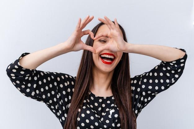 Ritratto di una donna adorabile che fa cuore con le dita. sfondo bianco.